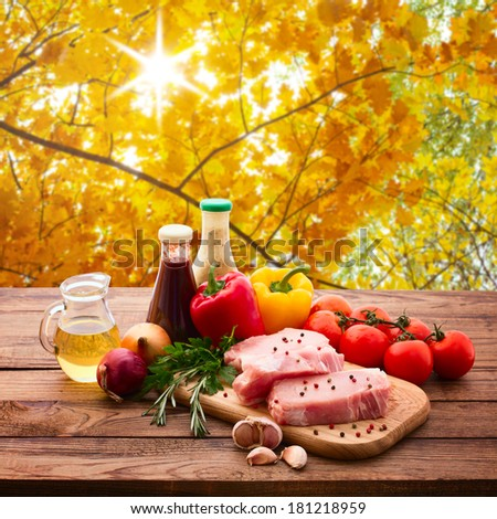 Food raw meat for barbecue with fresh vegetables on wooden surface, meat raw steak, beef steak bbq, tomatoes, peppers, spices for cooking meat. Autumn landscape collage. - stock photo