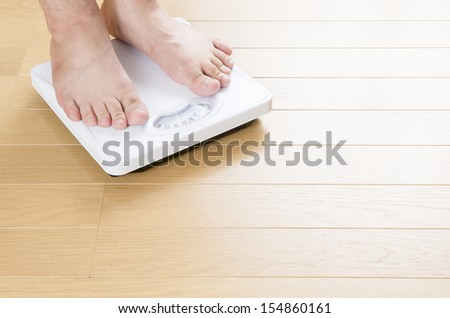 Foot of man standing on bathroom scale - stock photo