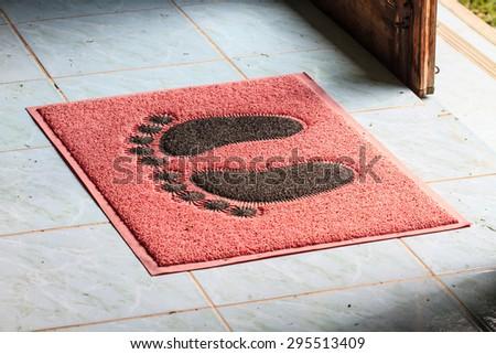 foot on doormat with open door close up - stock photo