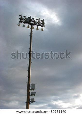 football stadium light tower with stormy sky and room for text - stock photo