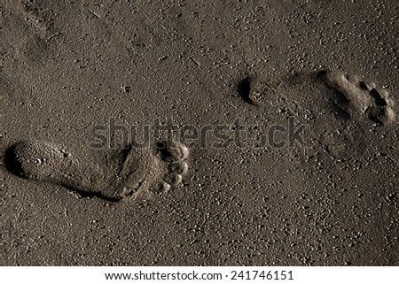2 footprints in the sand - stock photo