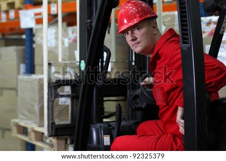 forklift driver worker in red uniform and safety helmet in storehouse portrait - stock photo