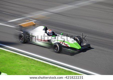 Formula 2.0  race car racing on speed track with motion blur at summer day