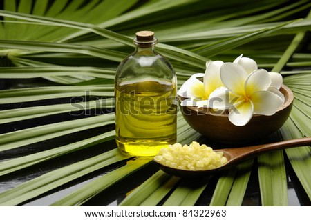 Frangipani flower in bowl and massage oil and bath salt in wood spoon on palm leaf - stock photo