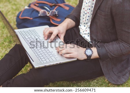 freelancer from the device: laptop, tablet, player, notebook, lying on the grass and working