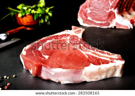 Fresh and raw meat. Ribeye. Uncooked steaks grilled BBQ on black background blackboard. Grilled meat and barbecue, steaks uncooked meat. BBQ - stock photo