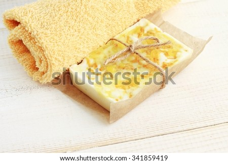 Fresh bar of handmade honey balmy soap, soft yellow hand towel. Healthy hygiene and skincare.  - stock photo