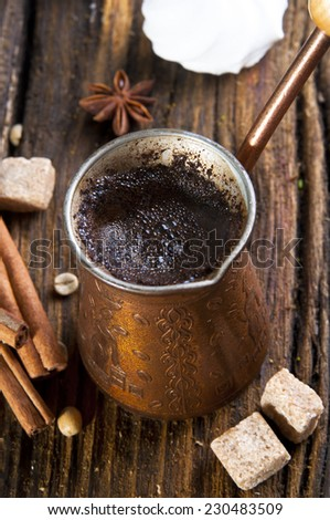 Fresh coffee in cezve with cinnamon and brown sugar on wooden table - stock photo