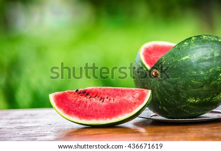 Fresh Cut watermelon on a wooden table in the garden. - stock photo