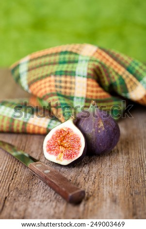 fresh figs, old knife and chequered towel on rustic wooden table