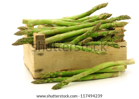 fresh green asparagus shoots in a wooden crate on a white background