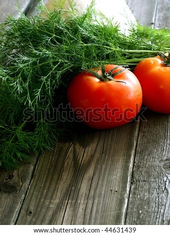 fresh green dill and tomatoes on wooden boards