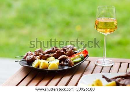 Fresh grilled meat and vegetables served outdoors - stock photo