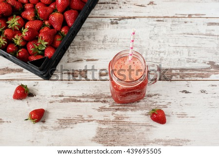 Fresh juice, shake, milkshake of strawberries in a mason jar with a straw. Pile of juicy ripe organic fresh strawberries in a black crate. Strawberry fresh drink. Light rustic wooden background  - stock photo