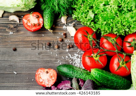 Fresh juicy ripe summer useful vegetables and greens, red tomatoes , cucumbers , cabbage , lettuce , basil , parsley , dill and salt and spices on a dark wooden background - stock photo