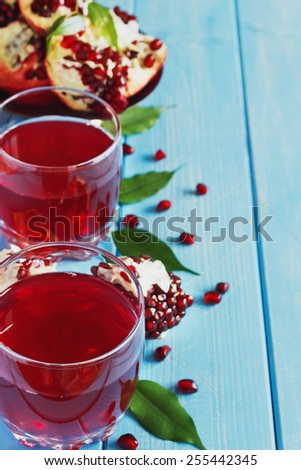 fresh pomegranate juice and ripe pomegranate seeds on a blue wooden background.health and diet food.  - stock photo