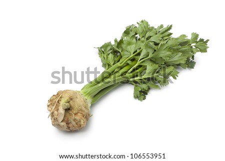 Fresh raw Celery root with green leaves on white background