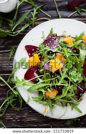 fresh salad with arugula, orange and beetroot, close up - stock photo