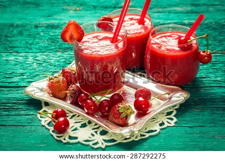 fresh strawberry and cherries smoothie on a wooden background. Summer detox drink and refreshment organic concept.Vintage filter. - stock photo