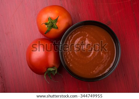 2 fresh tomato with tomato paste or puree or ketchup in black bowl, isolated on red wooden background, top view - stock photo