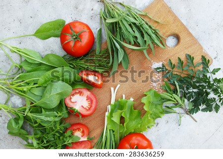 Fresh tomatoes with herbs on a wooden board