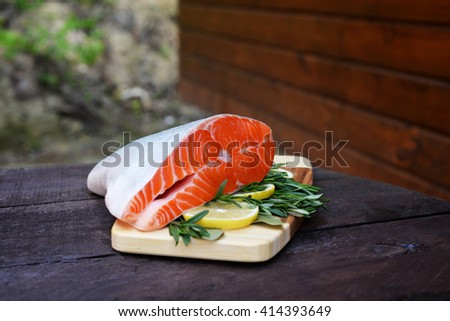 fresh uncooked salmon  with fresh herbs. fish with rosemary on wood. Piece of a salmon with lemon on wooden background - stock photo