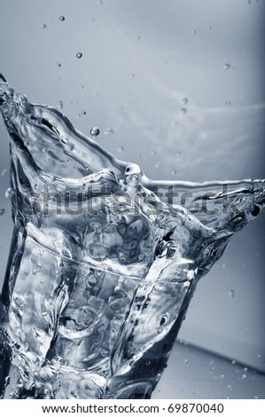 Fresh water splashing out of a glass with ice cubes  over gradient background - stock photo