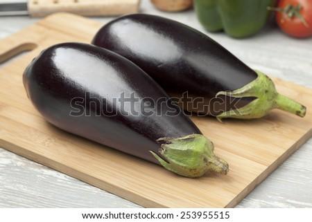 Fresh whole purple eggplants on a cutting board - stock photo