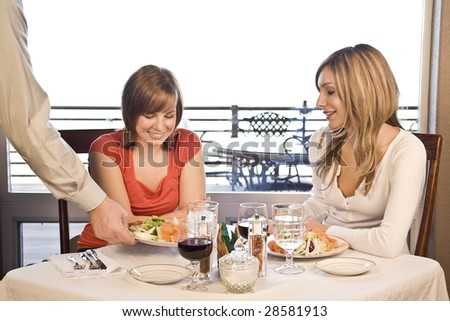 2 friends eating lunch at a cafe with a waiter brining food - stock photo