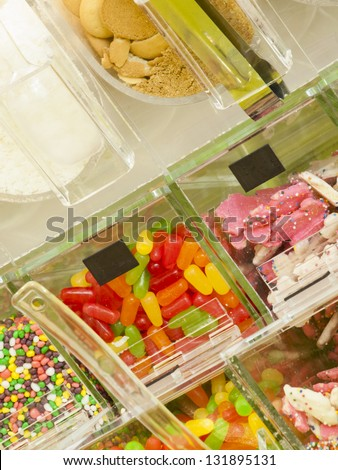 �¢??Frozen yogurt toppings bar. Yogurt toppings ranging from fresh fruits, nuts, fresh-cut candies, syrups and sprinkles.