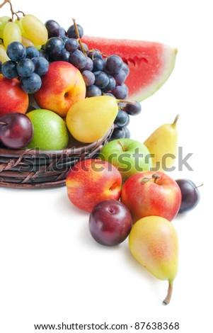 Fruits. Various fresh ripe fruits placed in a wicker basket and around on white background. - stock photo