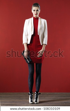 Full body fashion model holding little purse - stock photo