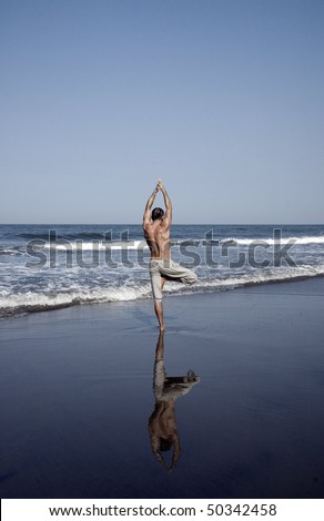 Full body shot of the man doing yoga on a beach, Goa, India - stock photo