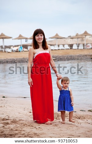 full length shot of mother with  toddler walking  on sand beach