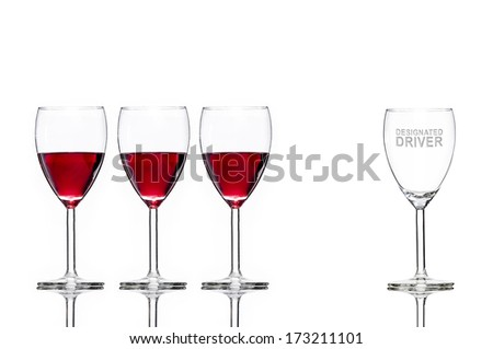 3 full wine glasses and 1 empty wine glass for the designated driver, encouraging the viewer to not drink and drive  - stock photo