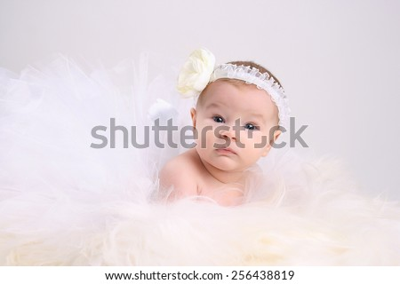 funny beautiful little girl in a white skirt, and a pack with a white bandage on his head lies on fur - stock photo