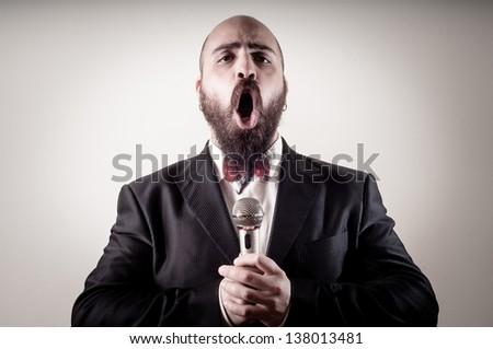 funny elegant singer bearded on vignetting background - stock photo