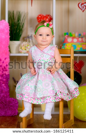 funny little kid in first birthday with colored balloons in the bright room  laughing  - stock photo
