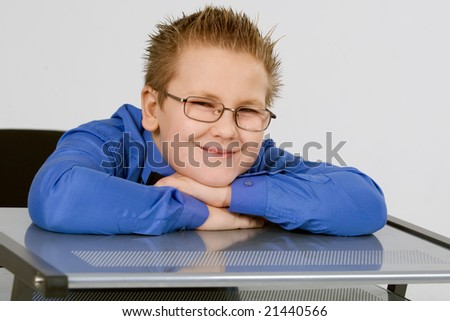 Funny schoolboy leaning on school desk