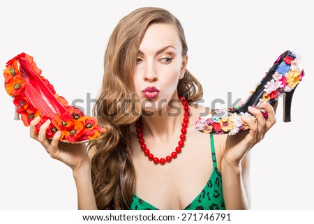 Funny shopping woman isolated over white background, dilemma what shoes to choose - stock photo