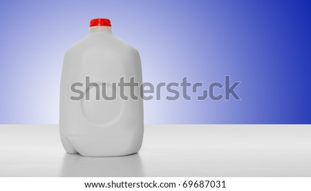 1 Gallon of Milk in a milk carton on a shiny table with blue background background. - stock photo