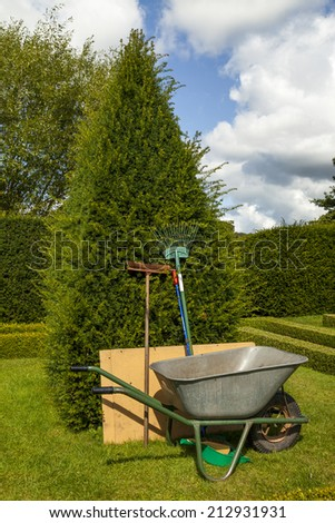 Garden tools leaning upright against yew tree next to a wheel barrow in an Elizabethan style knot garden . - stock photo