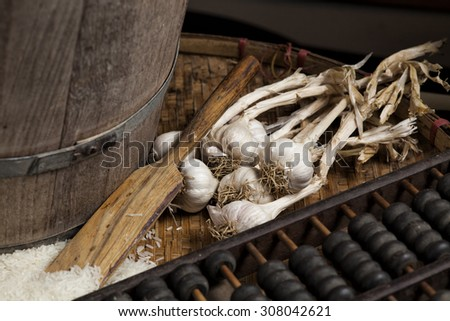 garlic,Uncooked rice, on a wooden tray , still life - stock photo