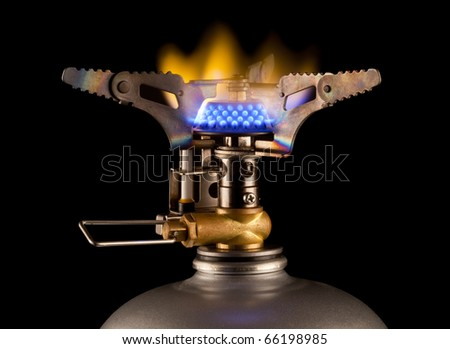 gas burner with blue flame on black background - stock photo