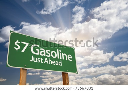 $7 Gasoline Green Road Sign with Dramatic Clouds, Sun Rays and Sky.
