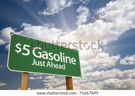 $5 Gasoline Green Road Sign with Dramatic Clouds, Sun Rays and Sky. - stock photo