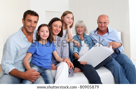 3-generation family looking at photo album - stock photo