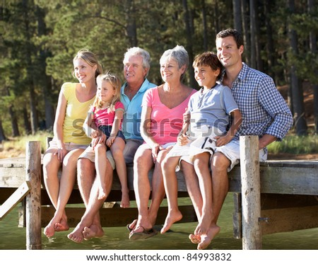 3 Generation family sitting by lake - stock photo