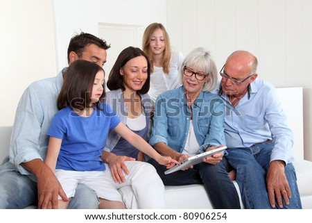 3-generation family sitting in couch with electronic tablet - stock photo