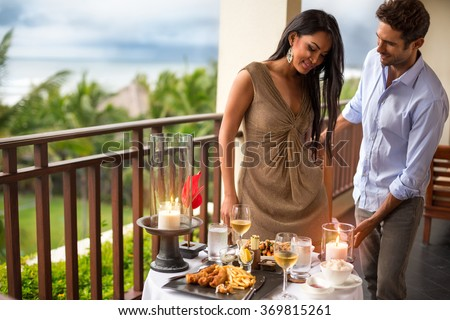 gentleman with his girl on dinner, helping her accommodated to the table - stock photo